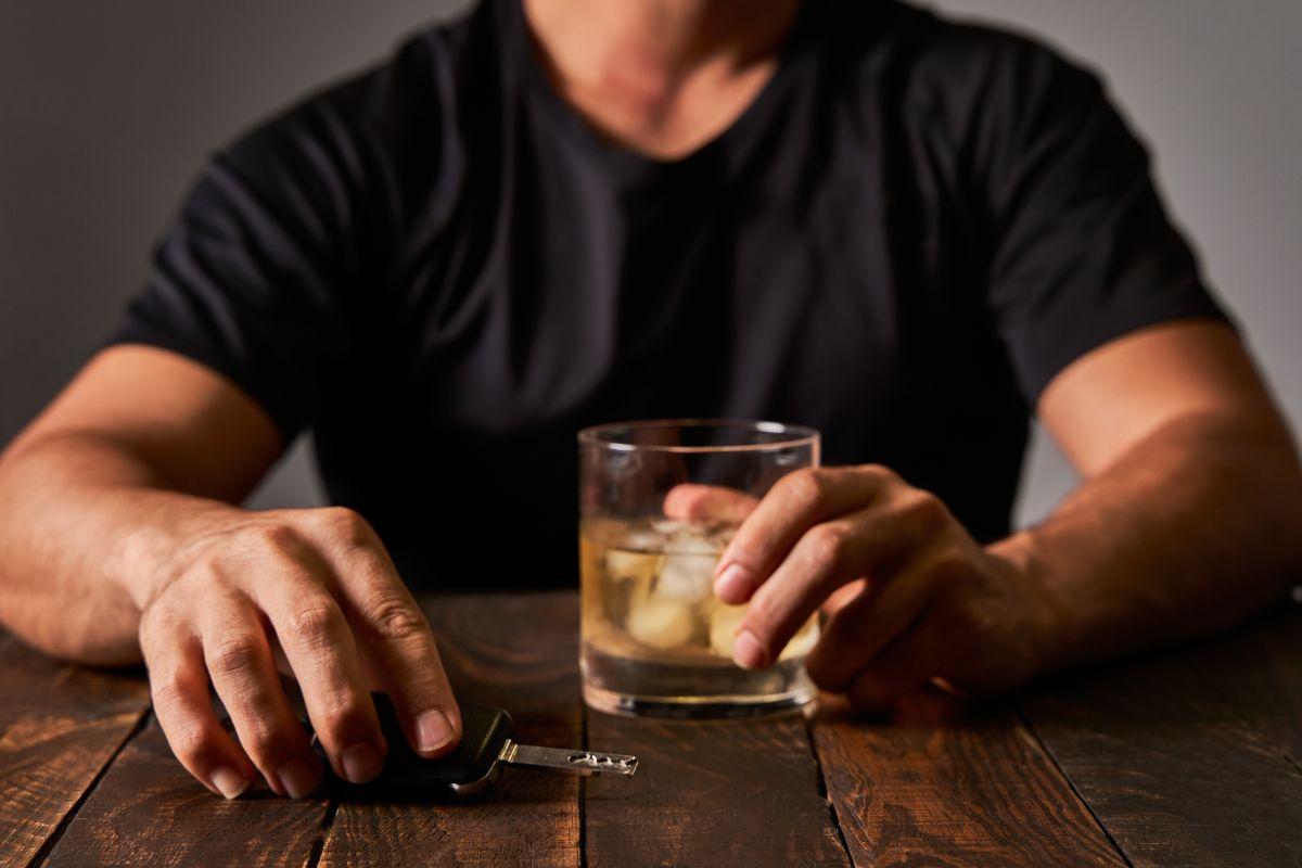 alkohol i kluczyki w dłoni mężczyzny